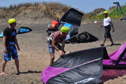 allievo che appoggia kitesurf sulla spiaggia